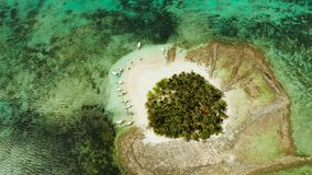 Tropical Guyam Island with a sandy beach and tourists. Aerial view of sandy beach with tourists on tropical island with palm trees and turquoise water. Guyam stock footage