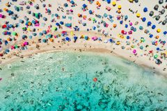 Aerial view of sandy beach with umbrellas and sea. Aerial view of sandy beach with colorful umbrellas, swimming people in sea bay with transparent blue water in royalty free stock photography