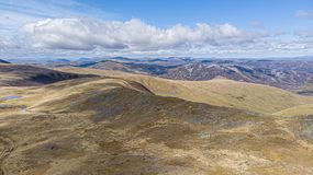 An aerial view of a Scottish mountain range with small lake and trail path in the foreground under a majestic blue sky and white. Clouds stock image