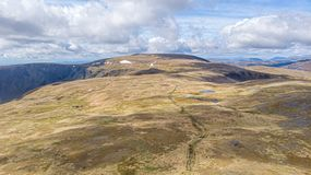 An aerial view of a Scottish mountain summit plateau with heather, trail path and huge cliff under a majestic blue sky and huge. White clouds stock photos