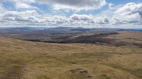 An aerial view of a Scottish mountain summit plateau with heather and trail path  under a majestic blue sky and huge white clouds.  royalty free stock photos