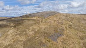 An aerial view of a Scottish rocky Munro summit with trail path under a majestic blue sky and white clouds.  royalty free stock photo