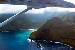 Small prop airplane flies over Maui`s tall sea cliffs. Aerial view of sea cliffs, Pacific surf, and fog on the coast of the island of Molokai in Hawaii, showing royalty free stock photos