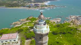 Aerial view sea light house on rocky island in blue sea and modern city on skyline. Drone view lighthouse tower on green. Island in ocean stock video