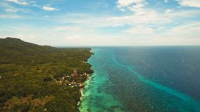 Seascape with tropical island, beach, resort, hotels. Bohol, Anda area, Philippines. Aerial view: sea and the tropical island with beach,resort, hotels stock footage