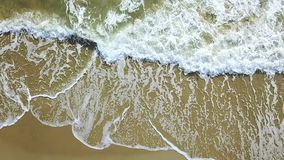 Aerial view of the sea waves crashing on the beach. Aerial survey. Slow motion. Aerial drone footage of the sea waves forming a fine white foam reaching the stock video footage