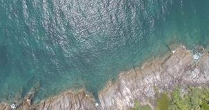 Aerial view of sea waves crashing on rocks of tropical island. Aerial drone view of beautiful waves and sea shore cliff with green palms stock footage
