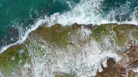 AERIAL VIEW. Sea waves splashing with foam and spray to stony coast. Beautiful woman lies on rocky beach. stock video footage