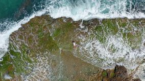 AERIAL VIEW. Sea waves splashing with foam and spray to stony coast. Beautiful woman lies on rocky beach.