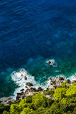 Aerial view of seashore with blue sea and fresh green vegetation Royalty Free Stock Image