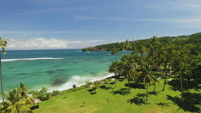 Aerial view of Senggigi beach in Lombok, Indonesia. Aerial view of Senggigi beach with turquoise water, flying through green lawn and palm trees in Lombok island stock video