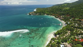 Aerial view of Senggigi beach in Lombok, Indonesia. Aerial view of Senggigi beach with turquoise water in Lombok island covered by green trees, some hotels on stock footage