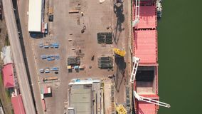 Aerial view of the ship loading near the berth in the port. Loading the wire rod. Aerial view of the ship`s loading near the berth in the cargo port during the stock video