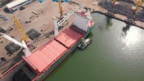 Aerial view of the ship loading near the berth in the port. Loading the wire rod. Aerial view of the ship`s loading near the berth in the cargo port during the stock video footage