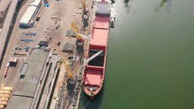 Aerial view of the ship loading near the berth in the port. Loading the wire rod. Aerial view of the ship`s loading near the berth in the cargo port during the stock footage