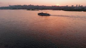 Aerial view of the ship sailing on the river in the city at sunset. royalty free stock photography