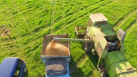 AERIAL VIEW. Combine Harvester Unloading Wheat Grain Into The Tractor Trailer. stock video footage