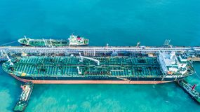 Aerial view shot of crude oil tanker ship anchored at the oil te. Rminal at port Stock Photos
