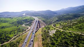 Aerial view shot flying over green hills fields, presents highway road and modern bridge with driving cars Royalty Free Stock Photos
