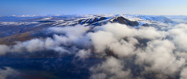 Aerial view Siberian mountain landscape with peaks covered by snow and cloud Stock Photography