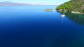 Aerial view of Siderona bay, Corinthia, Greece, on a lovely bright day in a calm blue and turquoise sea, with sailing boat