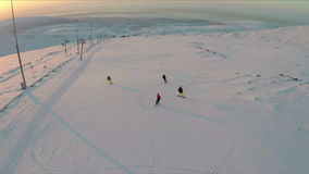 Aerial view of skiers and snowboarders at sunset stock video