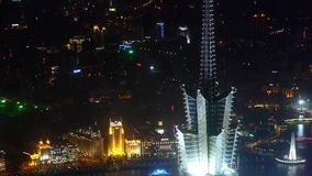 Aerial view of skyscraper rooftop crown at night,shipping & urban traffic. Elevated view of high-rise buildings rooftop crown with river at night in stock video footage