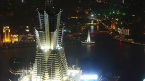 Aerial view of skyscraper rooftop crown at night,shipping & urban traffic. Elevated view of high-rise buildings rooftop crown with river at night in stock footage