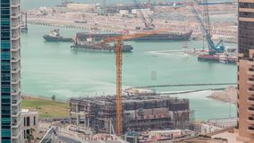 Aerial view of a skyscraper under construction with huge cranes timelapse in Dubai marina. Ship on a background. United Arab Emirates stock footage