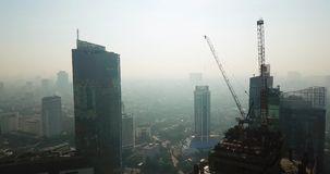 Aerial view of skyscrapers construction site. JAKARTA, Indonesia - June 08, 2018: Aerial view of skyscrapers construction site with cranes on the top in Jakarta stock video