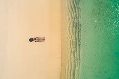Aerial view of slim woman sunbathing lying on a beach chairin Seychelles. Summer seascape with girl, beautiful waves, colorful royalty free stock photography