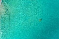 Aerial view of slim woman swimming on the swim mattress in the t royalty free stock photo