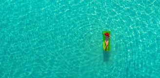Aerial view of slim woman swimming on the swim mattress in the transparent turquoise sea in Seychelles. Summer seascape with girl. Beautiful waves, colorful royalty free stock photos