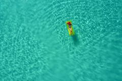 Aerial view of slim woman swimming on the swim mattress in the transparent turquoise sea in Seychelles. Summer seascape with girl. Beautiful waves, colorful royalty free stock images