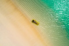 Aerial view of slim woman swimming on the swim mattress in the transparent turquoise sea in Seychelles. Summer seascape with girl stock images