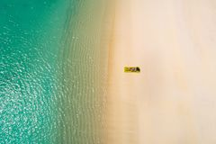 Aerial view of slim woman swimming on the swim mattress in the transparent turquoise sea in Seychelles. Summer seascape with girl stock image