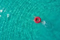 Aerial view of slim woman swimming on the swim ring donut in th stock images