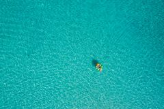 Aerial view of slim woman swimming on the swim ring donut in th stock photos