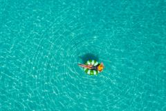Aerial view of slim woman swimming on the swim ring donut in th stock photo
