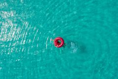Aerial view of slim woman swimming on the swim ring donut in the transparent turquoise sea in Seychelles. Summer seascape with stock photo
