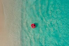 Aerial view of slim woman swimming on the swim ring donut in the transparent turquoise sea in Seychelles. Summer seascape with. Girl, beautiful waves, colorful royalty free stock photo
