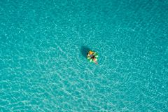 Aerial view of slim woman swimming on the swim ring donut in the transparent turquoise sea in Seychelles. Summer seascape with. Girl, beautiful waves, colorful stock images