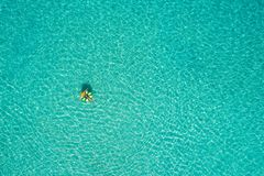 Aerial view of slim woman swimming on the swim ring donut in the transparent turquoise sea in Seychelles. Summer seascape with. Girl, beautiful waves, colorful royalty free stock images