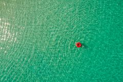 Aerial view of slim woman swimming on the swim ring donut in the transparent turquoise sea in Seychelles. Summer seascape with. Girl, beautiful waves, colorful stock photos