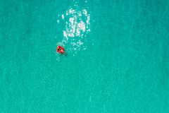 Aerial view of slim woman swimming on the swim ring donut in the transparent turquoise sea in Seychelles. Summer seascape with. Girl, beautiful waves, colorful royalty free stock image