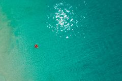 Aerial view of slim woman swimming on the swim ring donut in the transparent turquoise sea in Seychelles. Summer seascape with. Girl, beautiful waves, colorful stock photography