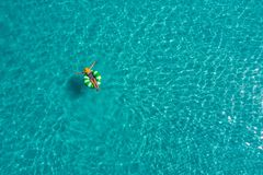 Aerial view of slim woman swimming on the swim ring donut in the transparent turquoise sea in Seychelles. Summer seascape with. Girl, beautiful waves, colorful royalty free stock photography