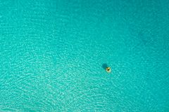 Aerial view of slim woman swimming on the swim ring  donut in the transparent turquoise sea in Seychelles. Summer seascape with. Girl, beautiful waves, colorful stock photo