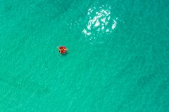 Aerial view of slim woman swimming on the swim ring  donut in the transparent turquoise sea in Seychelles. Summer seascape with. Girl, beautiful waves, colorful stock image