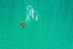 Aerial view of slim woman swimming on the swim ring  donut in the transparent turquoise sea in Seychelles. Summer seascape with royalty free stock images